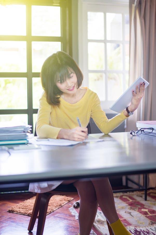Estudantes de mulher asiáticos novos que usam tabuletas e escrevendo a nota na faculdade foto de stock royalty free