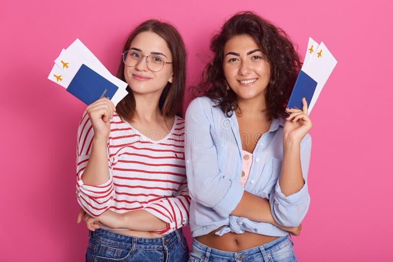 Estudantes de mulheres extáticos novos que guardam passaportes com as camisas srylish dos bilhetes, vestir da passagem de embarqu imagens de stock