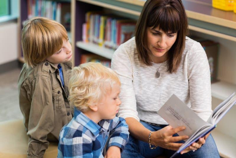 Estudantes de Reading Book For do professor na biblioteca fotos de stock royalty free