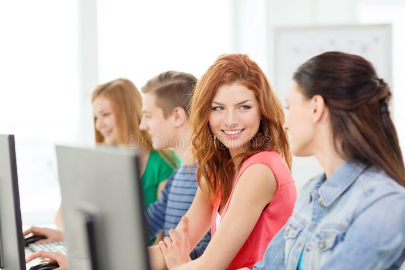Estudantes de sorriso na classe do computador na escola fotos de stock