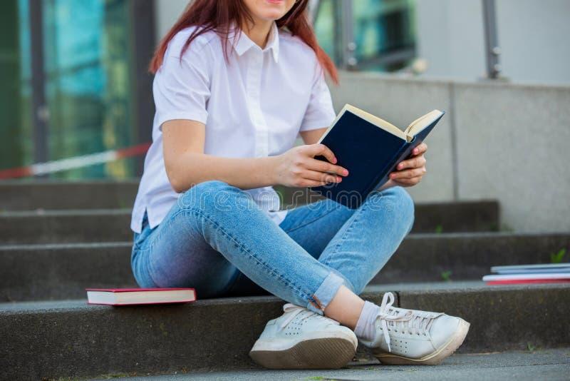 Estudantes de sorriso novos que guardam fora livros foto de stock royalty free