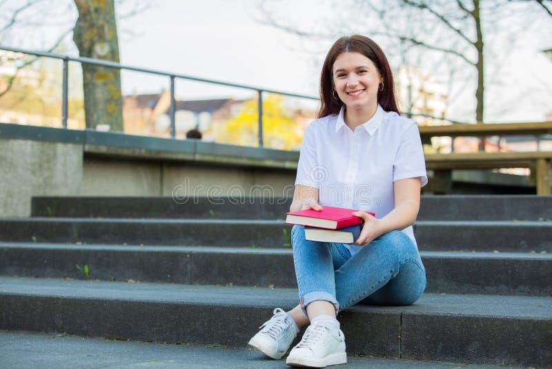 Estudantes de sorriso novos que guardam fora livros fotografia de stock royalty free