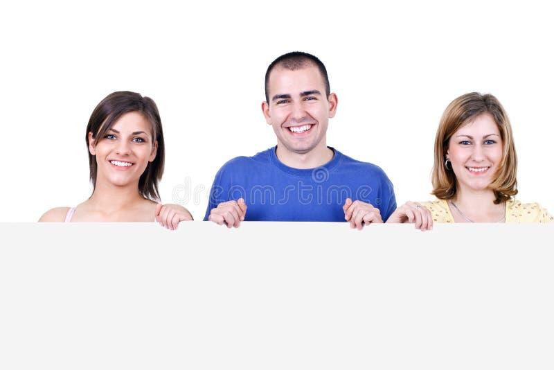 Estudantes de sorriso que prendem um quadro de avisos imagens de stock royalty free