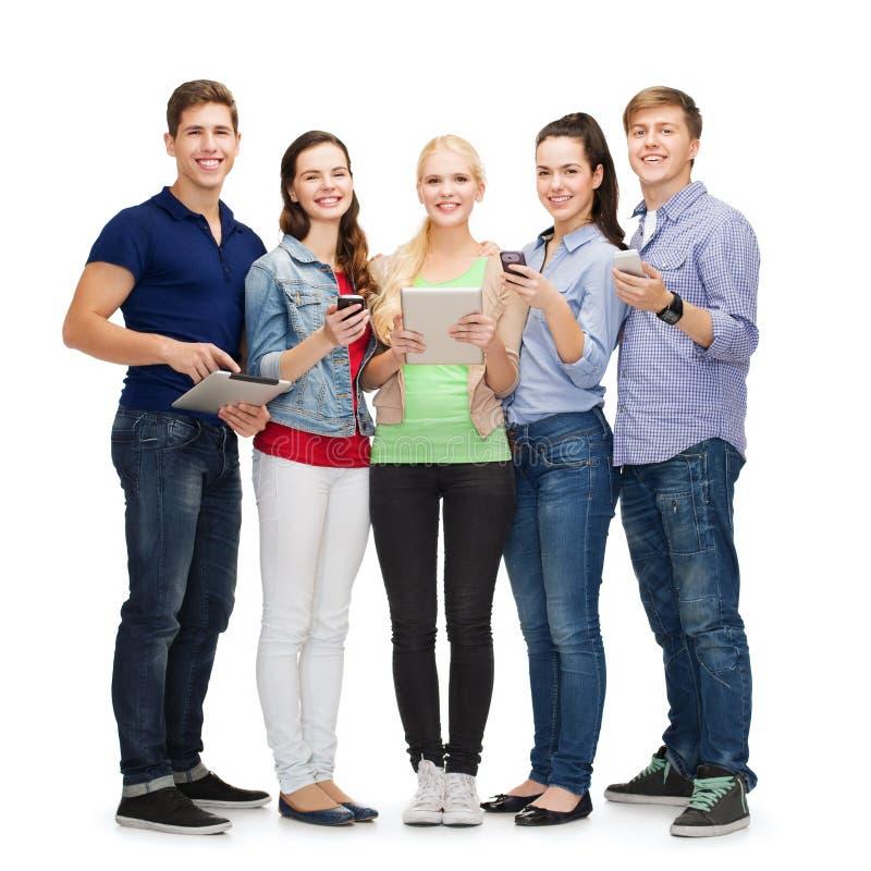 Estudantes de sorriso que usam smartphones e PC da tabuleta fotografia de stock