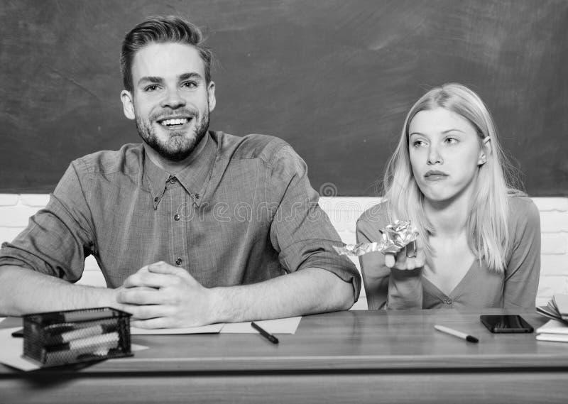 Estudantes despreocupados Apreciando o tempo na faculdade O indiv?duo e a menina sentam a sala de aula Estudo na faculdade ou na  imagens de stock royalty free