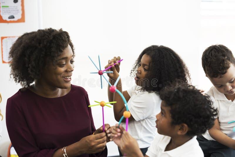 Estudantes diversos do jardim de infância que guardam a aprendizagem de estruturas de t imagens de stock royalty free