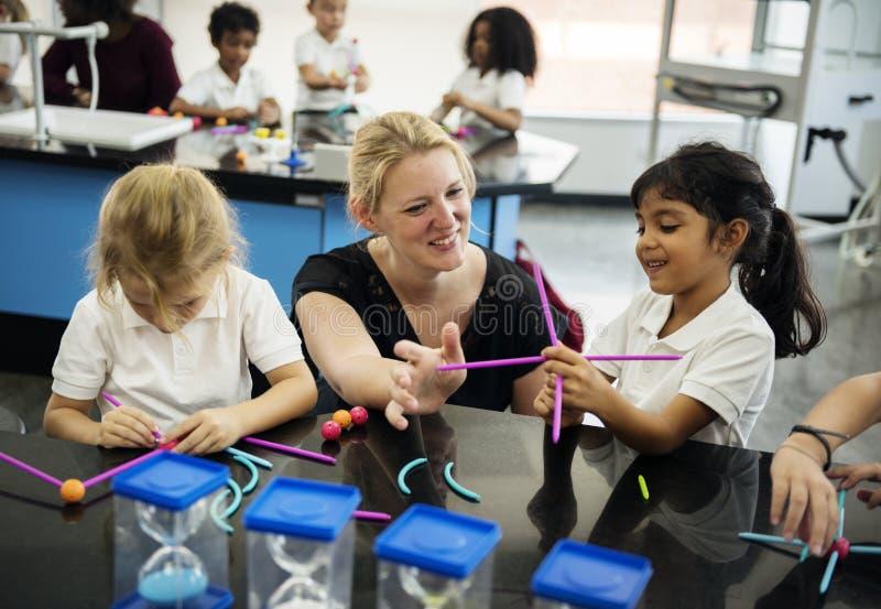 Estudantes diversos do jardim de infância que guardam a aprendizagem de estruturas de t imagem de stock royalty free