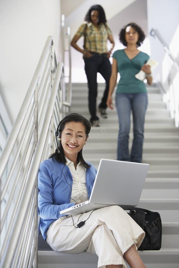 Estudantes do professor Using Laptop While que andam abaixo da escadaria imagens de stock