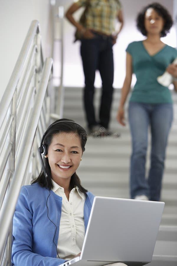Estudantes do professor Using Laptop While que andam abaixo da escadaria imagem de stock