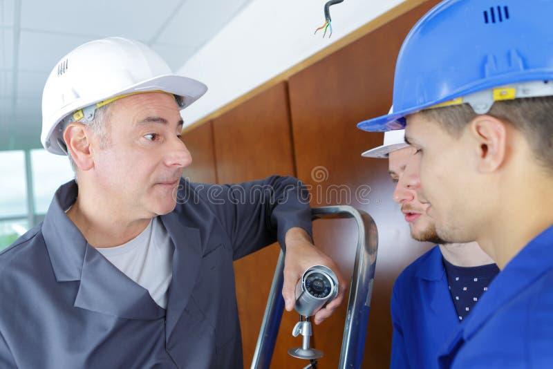 A estudantes do técnico dizendo como a instalar a câmara de vigilância video fotos de stock
