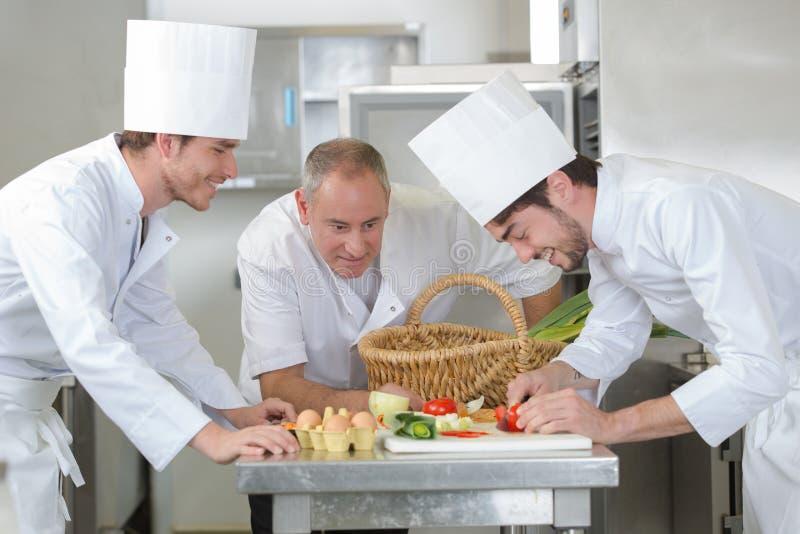 Estudantes do treinamento do cozinheiro chefe na cozinha do restaurante foto de stock