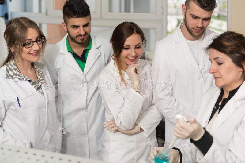 Estudantes dos cientistas com professor In Lab Classrom imagens de stock