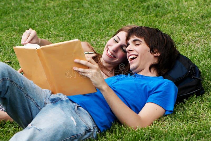 Estudantes dos pares que colocam na grama imagens de stock royalty free
