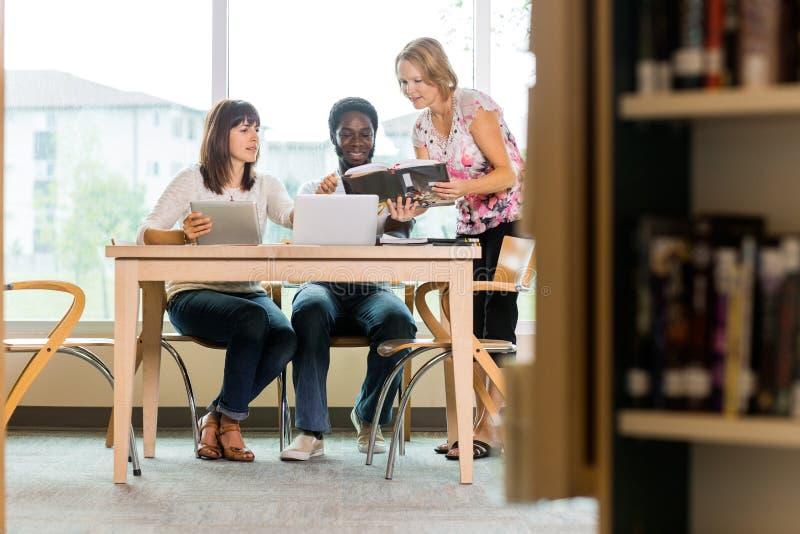 Estudantes e bibliotecário Looking At Book na biblioteca fotos de stock royalty free