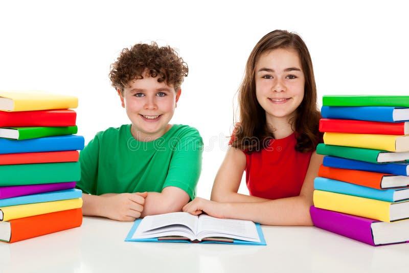 Estudantes e pilha dos livros fotografia de stock royalty free