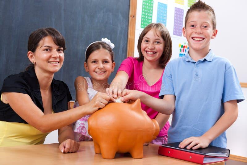 Estudantes e professor que põr a moeda no banco piggy imagens de stock royalty free