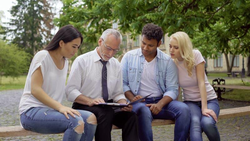 Estudantes e professor que sentam-se no parque perto da faculdade, discutindo o projeto da ciência imagens de stock royalty free
