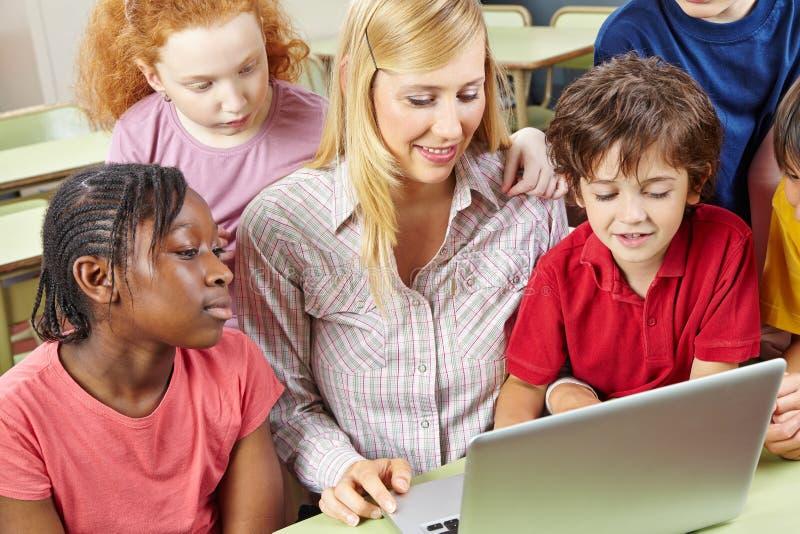 Estudantes e professor que trabalham com laptop imagem de stock
