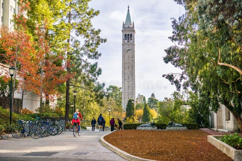 Estudantes e visitantes que andam através do terreno em um dia ensolarado do outono; foto de stock