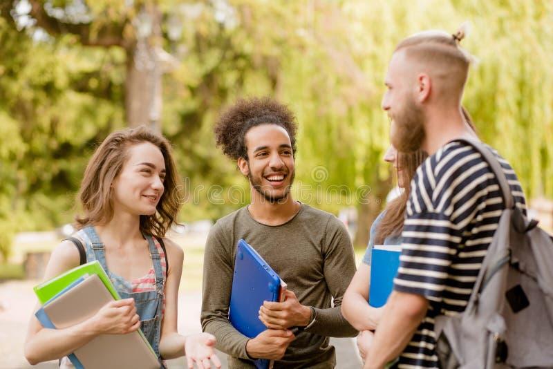 Estudantes em communacating do terreno, rindo foto de stock