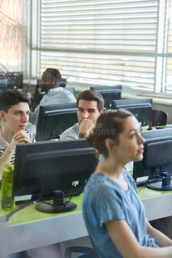 Estudantes em lições do curso de computador imagem de stock