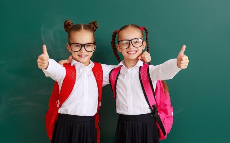 Estudantes engraçados dos gêmeos das meninas das estudantes das crianças sobre o quadro-negro da escola imagens de stock royalty free