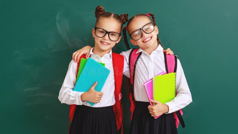 Estudantes engraçados dos gêmeos das meninas das estudantes das crianças sobre o quadro-negro da escola fotografia de stock