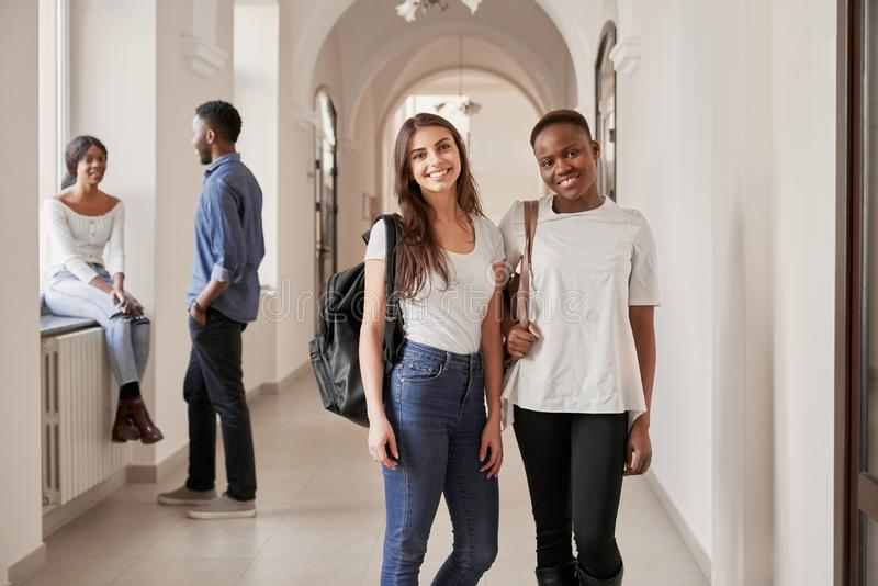 Estudantes f?meas africanos e caucasianos que descansam no corredor fotografia de stock royalty free