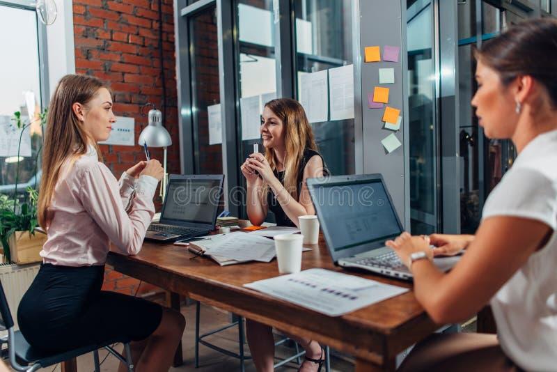 Estudantes fêmeas que trabalham na atribuição de escola usando os portáteis que sentam-se na mesa em uma sala de estudo imagem de stock
