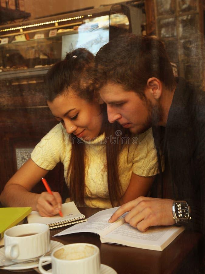 Estudantes felizes novos dos pares no café, vista através de uma janela fotografia de stock royalty free