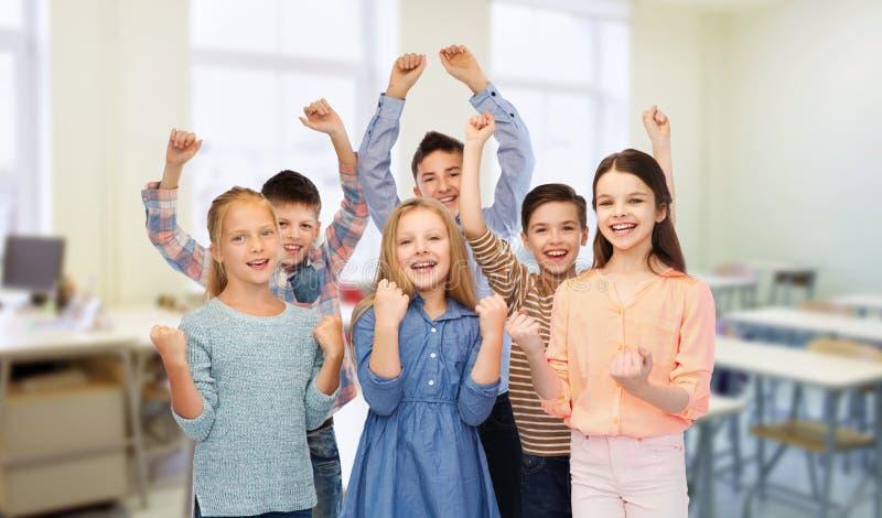 Estudantes felizes que comemoram a vitória na escola imagens de stock