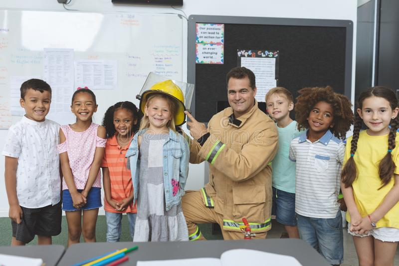 Estudantes felizes que estão com o sapador-bombeiro na sala de aula foto de stock royalty free