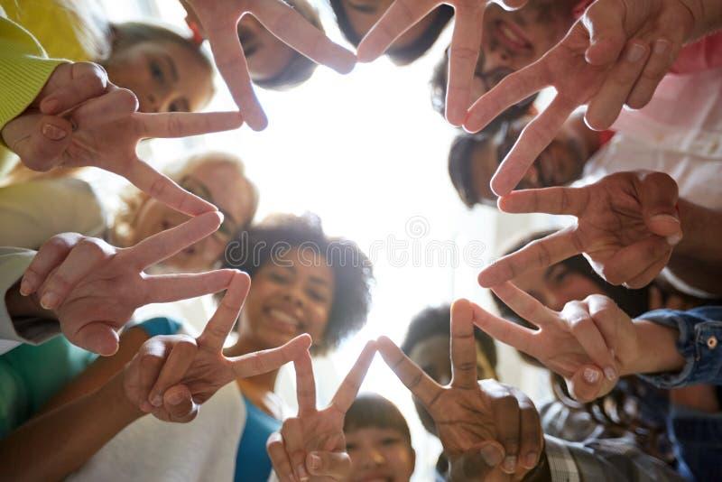 Estudantes internacionais que mostram a paz ou o sinal de v fotografia de stock