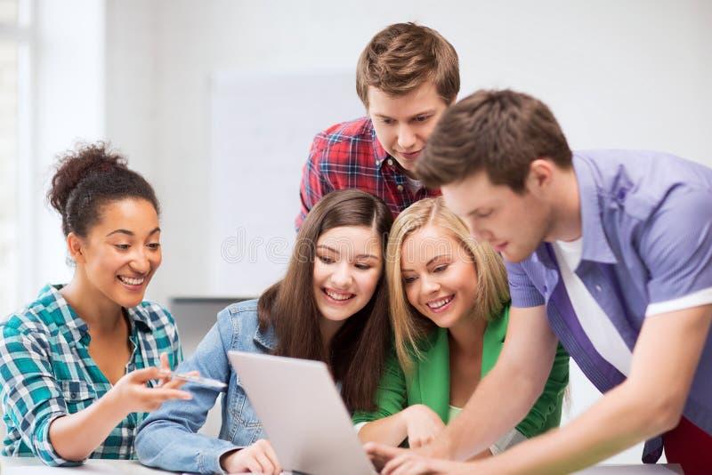 Download Estudantes Internacionais Que Olham O Portátil Na Escola Foto de Stock - Imagem de classmates, meninas: 33508422