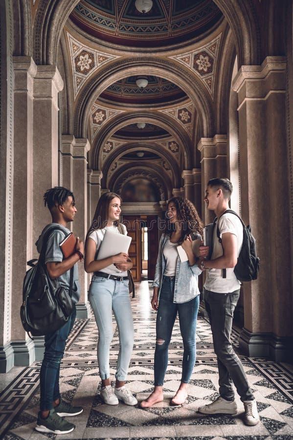 Estudantes junto Imagem completa do comprimento do grupo de estudantes bonitos que estão no salão da universidade e que conversam fotografia de stock royalty free