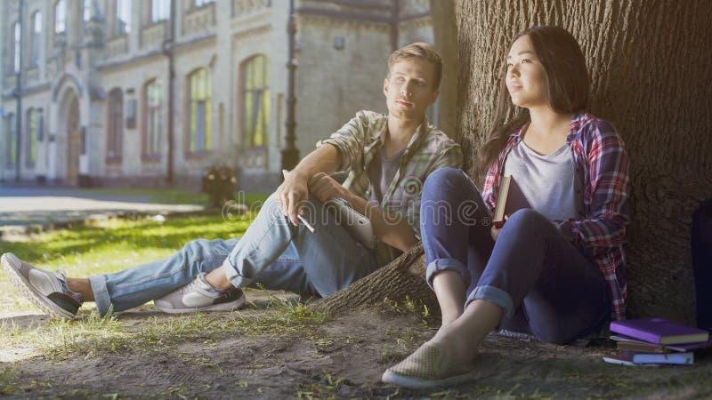 Estudantes masculinos e fêmeas multirraciais que sentam-se sob a árvore, anticipando, futuro imagem de stock royalty free