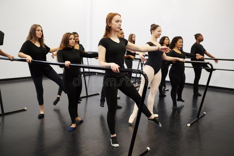 Estudantes Masculinos E Femininos Em Uma Escola De Artes Realizantes Ensaiando Balé No Dance Studio Usando Barre imagens de stock