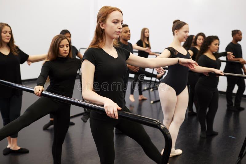 Estudantes Masculinos E Femininos Em Uma Escola De Artes Realizantes Ensaiando Balé No Dance Studio Usando Barre fotos de stock royalty free