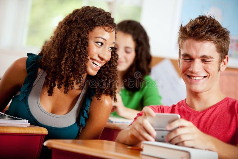 Estudantes: A menina olha sobre no telefone celular do indivíduo imagem de stock