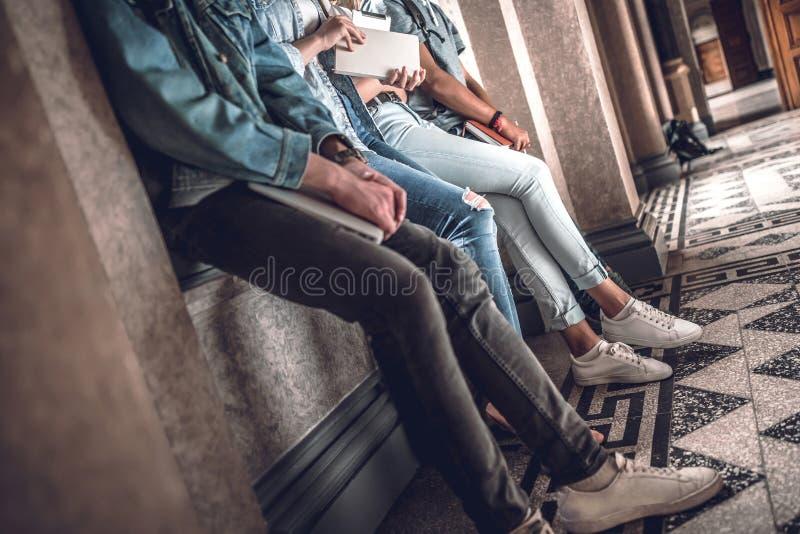 Estudantes modernos Tiro colhido dos jovens que gastam o toge do tempo foto de stock