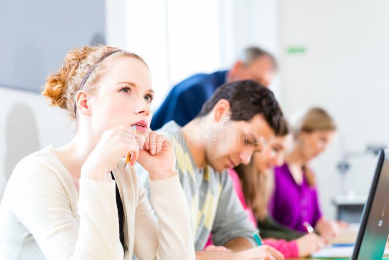 Estudantes no exame da escrita da faculdade imagens de stock
