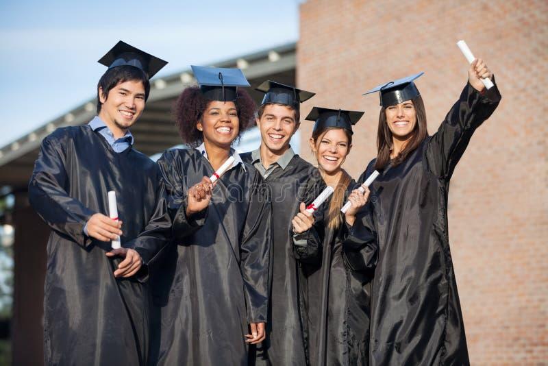 Estudantes nos vestidos da graduação que guardam diplomas sobre fotografia de stock