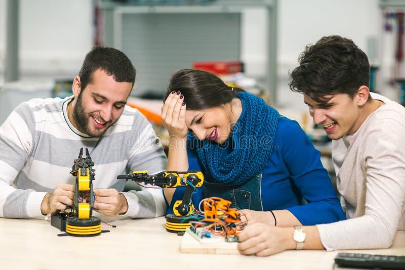Estudantes novos da robótica que preparam o robô para testar foto de stock