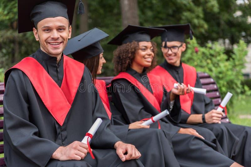 Estudantes novos felizes que comemoram sua graduação fotografia de stock royalty free