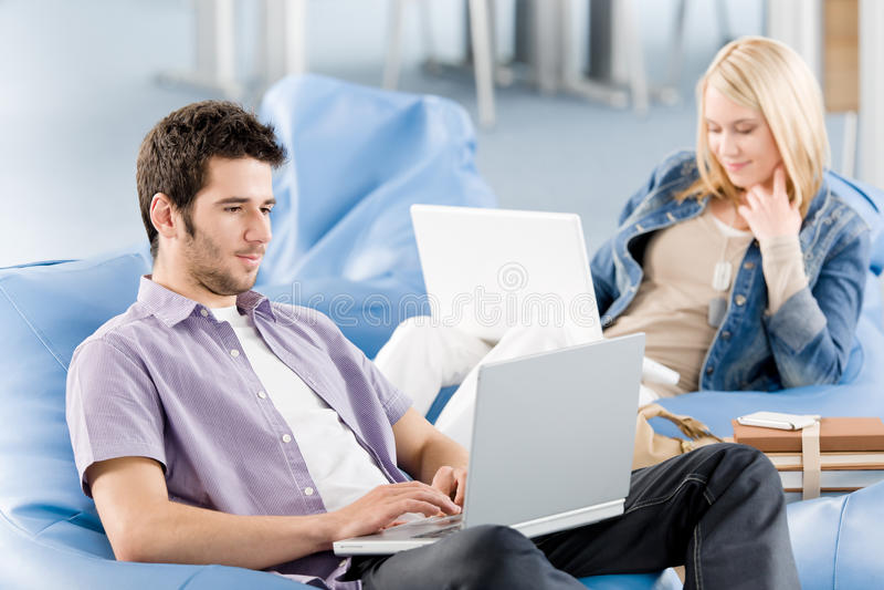 Estudantes novos na High School que trabalha no portátil imagens de stock royalty free