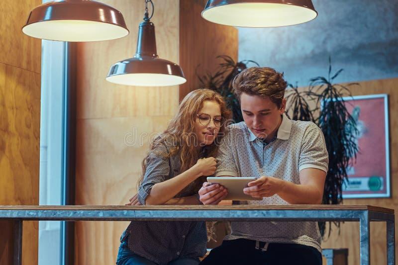 Estudantes novos pensativos dos pares que usam uma tabuleta digital ao sentar-se na tabela na cantina da faculdade durante uma ru fotografia de stock royalty free