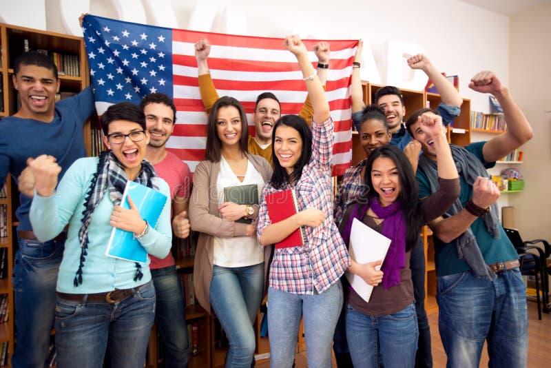 Estudantes novos que apresentam seu país com bandeiras fotografia de stock royalty free