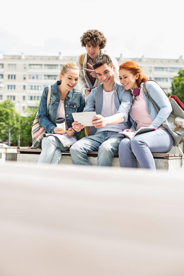 Estudantes novos que fotografam-se através da tabuleta digital no terreno fotos de stock