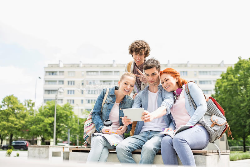 Estudantes novos que fotografam-se através da tabuleta digital no terreno da faculdade imagem de stock royalty free