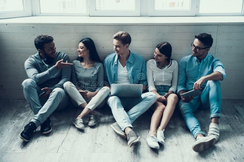Estudantes novos que sentam-se na faculdade com Gatgets fotos de stock
